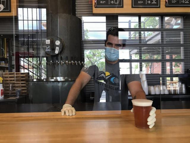 Ponysaurus Brewing has reopened with new safety precautions, including glass around the taproom bar, in the wake of COVID-19. (Courtesy of Ponysaurus)