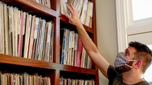 Ben Alschuler, 38, has thousands of records across all genres. He can remember where he was, physically and in life, when he acquired each record and he uses that memory to help organize his collection. (Photo by Elizabeth Ranatza)