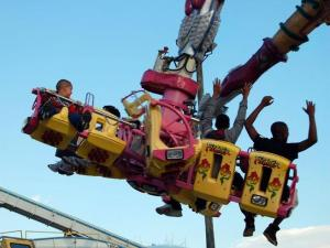 Fairgoers hang on while riding the Fighter.