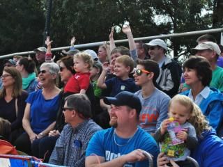 The crowd cheers racing pigs at Hogway Speedway during the NC State Fair.