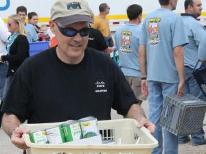 A volunteer at 2012's Food Lion Hunger Relief Day carries fairgoer donations to the truck.