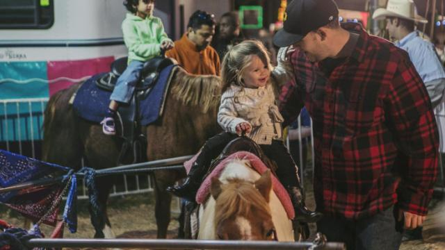 McKinney, 2, and her father, Josh Meekins, ride the ponies at the 2013 NC State Fair.