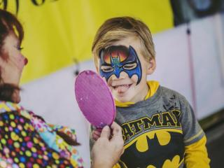 Charlie Gullette, 5, checks out his reflection at Mimi the Clowns' facepainting booth at the 2013 NC State Fair.