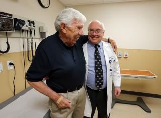 Jay Niederhauser hugs cardiologist Brent Muhlestein, right, of Intermountain Medical Center Heart Institute, at the end of an appointment in Murray on Tuesday, April 5, 2016. Niederhauser has lost 25 pounds. They talked about healthy living and loss of dangerous weight. (Deseret Photo)