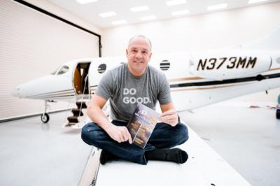 "Mark Patey sits on the wings of one of his planes holding his book, ""Addicts and Millionaires."" (Deseret Photo)"