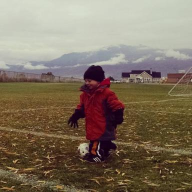 Arianne Brown's son dressed for the inclement weather as he kicks a soccer ball at his older brother's game. (Deseret Photo)