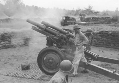 "One of twelve 105-mm howitzers of Wilber's battalion (152nd Field Artillery) fires ""over the American perimeter"" in Aitape, New Guinea, August 4, 1944. (Deseret Photo)"