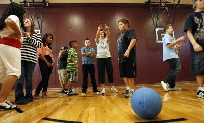Lyndsey Pearson and Cody Phelps instruct a 7th grade physical education class at Midvale Middle School before they play goal ball, Tuesday, Oct. 4, 2011. Arianne Brown writes about how she wishes her kids' school had the funding for a PE program. (Deseret Photo)