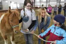Hayley Sumner, executive director and founder of Berkshire HorseWorks, center, assists Carlie Roberts, 10, left, and Anjani Taliercio, 8, right, as they try to lead Pumpkin during an Equine Assisted Psychotherapy open house on Saturday, March 18, 2017, at Berkshire Equestrian Center in Richmond, Mass. (Deseret Photo)