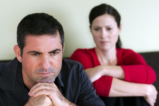 Portrait of unhappy young couple who have fallen out over a disagreement sitting on a sofa. Man in the front and the woman in the background. (Deseret Photo)