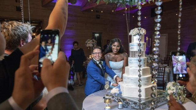 """Assaf Kedem and Erika Woods cut their wedding cake during the reception at the Barn at Shady Lane, outside Birmingham, Ala., Sept. 22, 2018. Once """"perfect strangers,"""" the two were drawn to each other's worlds. (Robert Rausch/The New York Times)"""