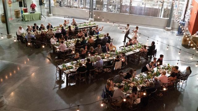 "Guests gather for dinner during Dr. Molly Larson and Whitney Morie's wedding reception at the Great Divide Brewing Company in Denver, Sept. 22, 2018. ""It's the story of a girl, another girl, an ovary and a series of leaps of faith."" (Dana Romanoff/The New York Times)"