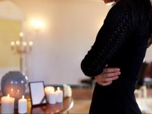cremation, people and mourning concept - close up of woman with