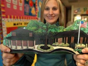 Second grade teacher Shannon Drizd holds a painting of Meadowview School in Grayslake, Ill., given to her by a student, Friday, Nov. 2, 2007. (AP photo/Paul Beaty)