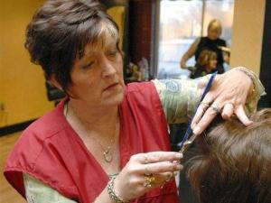 Pat Wiseman, who is a stylist at Escape Salon in Traverse City, Mich., works on a customer's hair on Monday, Nov. 19, 2007. (AP photo/John L. Russell)