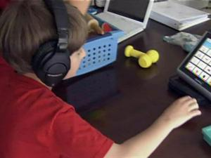 Austin Hodges uses a computer with icons to communicate and to help him overcome his autism and learn to speak again.