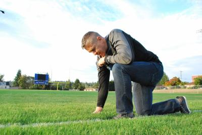 Coach Joe Kennedy prays on the football field. (Deseret Photo)