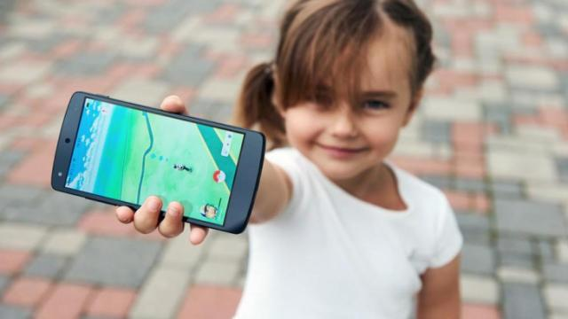 Riga, Latvia- July 17, 2016: Little girl playing a Pokemon Go game outdoors. Pokemon Go is a popular virtual reality game for mobile devices. The game allows players to capture, battle, and train virtual creatures, called Pokemon, who appear on device screens as though in the real world. (Deseret Photo)