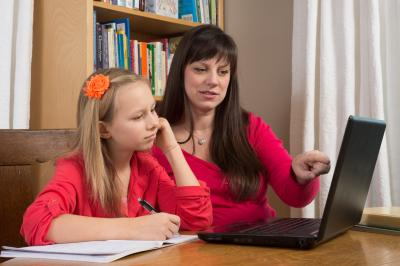 A mother and her young daughter sit in front of a laptop as they research information for her homework. (Deseret Photo)