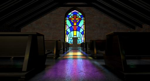 A dim old church interior lit by sun's rays penetrating through a colorful stained glass window in the pattern of a crucifix reflecting colors on the floor among rows of church pews. (Deseret Photo)