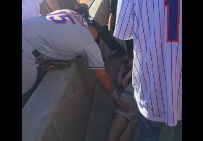 Tim Tebow prays over a fan who collapsed on Tuesday. (Deseret Photo)