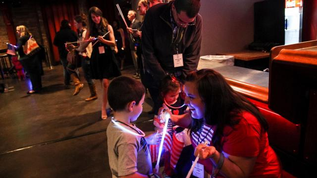 Casey and Lisa Child, of South Jordan, outfit their children, Devin, 4, and Heidi, 2, with glow sticks and light-up American flags at an election night party for independent presidential candidate Evan McMullin at The Depot in Salt Lake City on Tuesday, Nov. 8, 2016. (Deseret Photo)