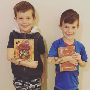 Carmen Rasmusen Herbert's sons Boston and Beckham hold their new books after meeting author Cressida Cowell and earning their dragon stamps of bravery and courage. (Deseret Photo)