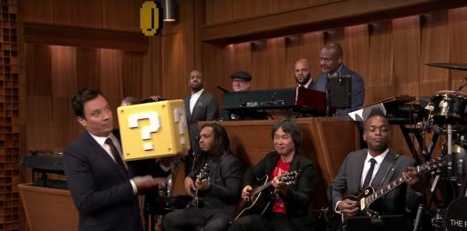 "Jimmy Fallon hits the coin box while The Roots and Shigeru Miyamoto play the ""Super Mario Bros. Theme."" (Deseret Photo)"