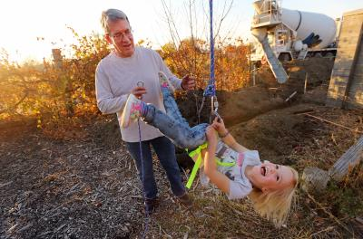Lynn Johnson tries to help his granddaughter Emma get off the zip line in his backyard in Draper Utah, as the grandchildren play on Monday, Nov. 7, 2016. (Deseret Photo)