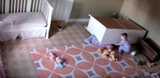 A toddler works to free his twin brother from fallen furniture. (Deseret Photo)