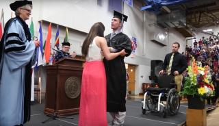 Chris Norton walks across the stage at his graduation with the help of his fiancé, Emily Summers. (Deseret Photo)