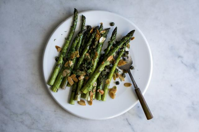 Asparagus, roasted plainly and quickly, is showered with flavorful capers, dill and almonds, in New York, March 31, 2018. Tread lightly when cooking asparagus. which is so delicate that it can be easily overwhelmed by neighboring ingredients in a dish. (Andrew Scrivani/The New York Times)