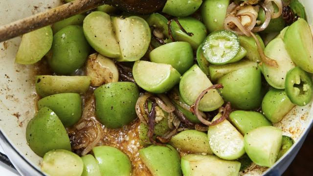 Tomatillo, onion and garlic are cooked for a braised chicken thigh dish, in New York, August 2018. Chicken thighs are ideal for quick weeknight braising because of their ability to become tender in a fraction of the time it takes other meats to reach the same result. Prop styled by Kalen Kaminski. (Michael Graydon & Nikole Herriott/The New York Times)