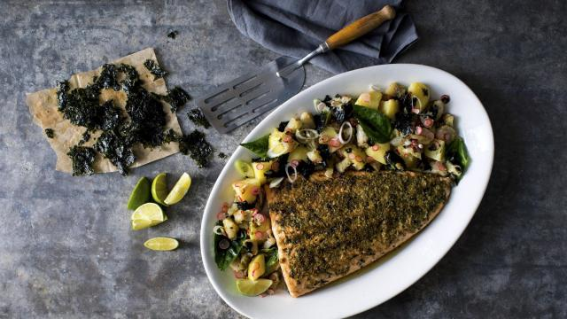 Salmon with browned butter and wakame seaweed, served alongside potatoes and sunchokes, in New York, Nov. 11, 2018. Yotam Ottolenghi's beloved late mother-in-law always made four types of meat and six carbs for festive family meals. He honors her memory — but serves salmon instead. (Andrew Scrivani/The New York Times)