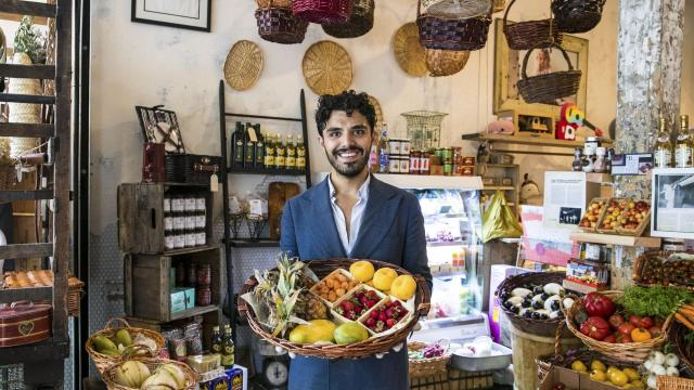 Daniel Soares, a fourth-generation Balducci, holds a fruit basket at Grace Balducci's Produce Market Pop-up, in New York, July 17, 2019. The shop features a selection of often hard-to-find ripe fruits and vegetables mostly from California, including yellow donut peaches, white cucumbers, blueberry grapes, baby pineapples and big, juicy golden kiwis. (Jeenah Moon/The New York Times)