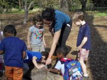 Kavanah Anderson of Duke Gardens shows kids a log