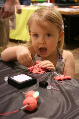 A girl tests at the conductive playdoh at the recent Makers Faire in Raleigh.