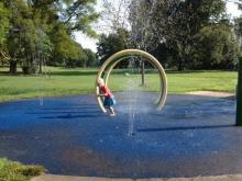 Playing on the sprayground at Forest Hills Park, Durham
