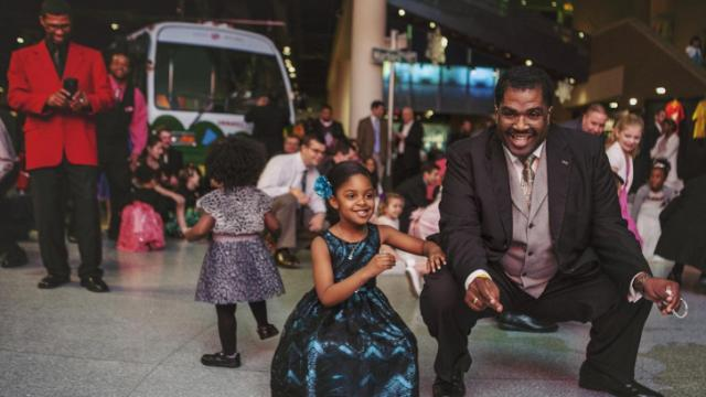 Kennedy Morehead, 5, gets down low during the Cha Cha slide with her dad, Rob, at the Triangle Father-Daughter dance on Saturday, Feb. 2.