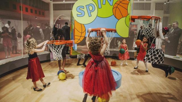 Girls play hoops in the sports room of the Marbles Kids Museum.