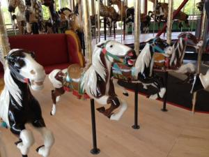 Several mini-ponies are perfect for the youngest carousel riders. A bench is right next to them for parents and caretakers.