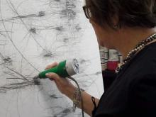Artist Kiki Farish works on a piece at Artspace in downtown Raleigh