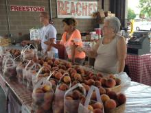 Selling peaches at the Pee Dee Orchards stand at the State Farmers' Market