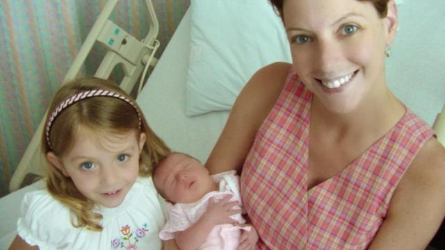 Jackie Hyland, after suffering a severe bout of morning sickness, prepares to leave the hospital with her newborn daughter and older daughter in July 2002.