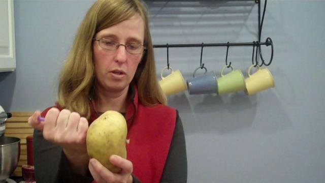 Beth Harris stabs a potato with a straw in a lesson about air pressure