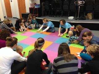 Catherine Hale (left in blue shirt) leads a SproutSongs class at Raleigh Music Academy.
