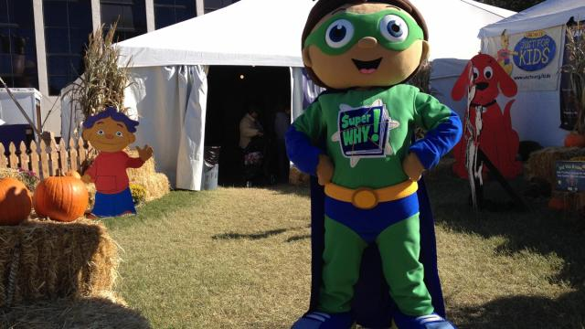 Super Why! poses in front of the UNC-TV tent at the fair