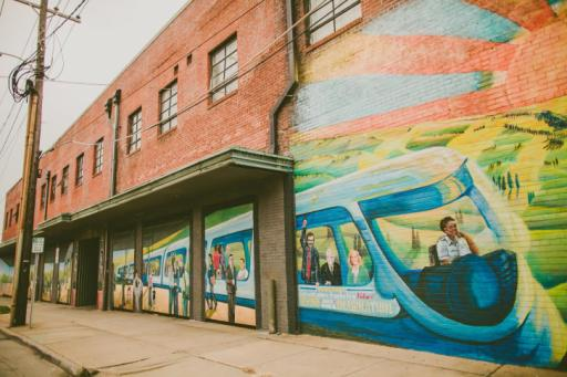 Warehouse district features brick buildings, murals as backdrops