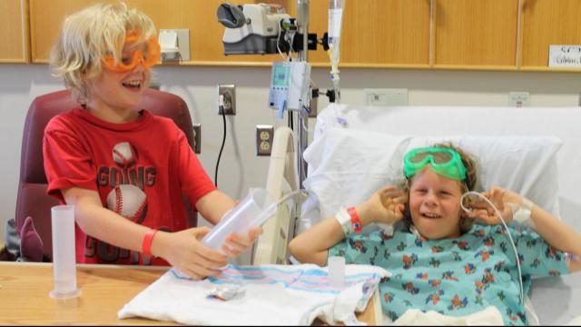 Two brothers shooting off rockets in their hospital room as part of the Wonder Connection, which brings science and nature programs to pediatric patients.