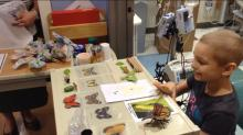 Pediatric patient Leah shows off her science fair project at UNC Children's Hospital.